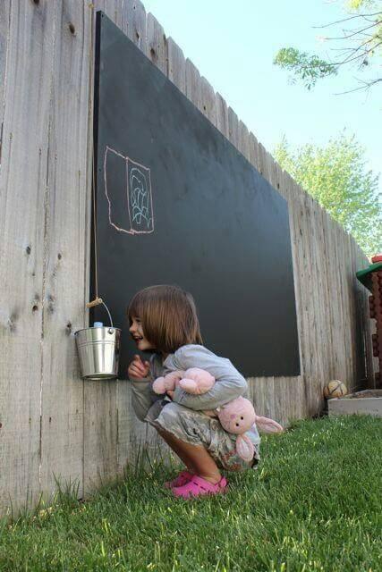 Ребёнок рисует на грифельной доске в саду